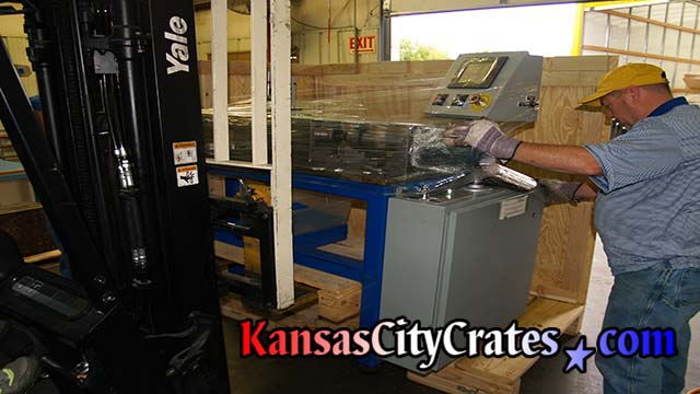 Stamping press wrapped and loading into industrial crate for international shipping