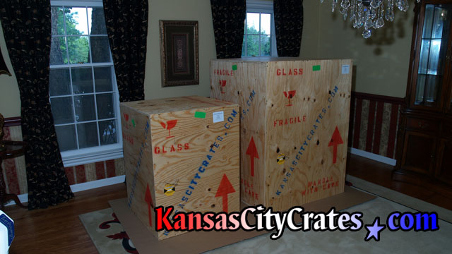 2 Large chandelier wood crates are sitting on cardboard in home waiting for shipping.