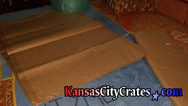 Blankets are laid out on floor before placing brown paper used to wrap items for crating.