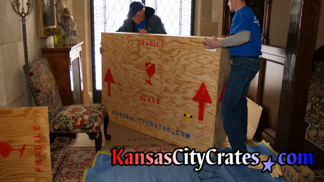 After crate is sealed it is moved from the furniture blanket onto thick cardboard until it is loaded into truck.