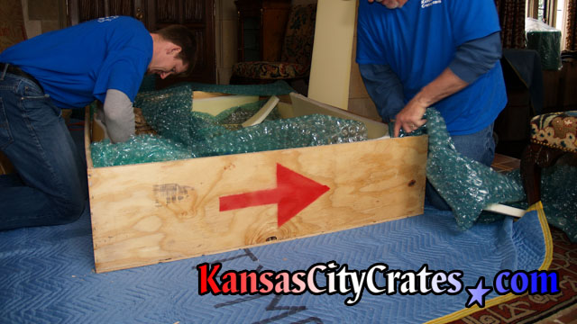 Wood export crate laying on furniture blanket with craters packing bubble wrap and foam inside to protect it.
