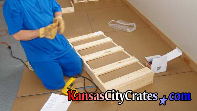 Crater closing domestic slat crate while working on cardboard in garage.
