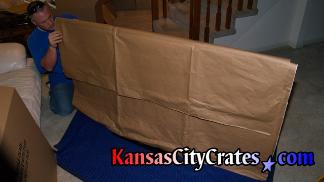 Paper wrapping is placed over LCD TV screen to protect it before bubble wrapping.