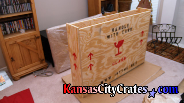 Crate sitting on carboard in carpeted home for flat panel tv.