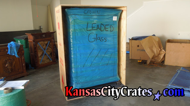 Bubble and stretch wrapped leaded glass cabinet loaded into crate