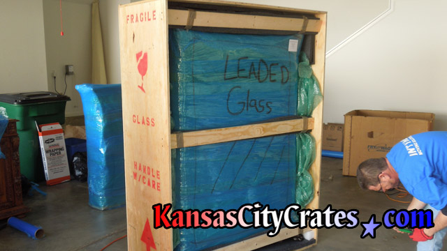 Fully wrapped leaded glass cabinet inside crate with bracing ready to seal shut.