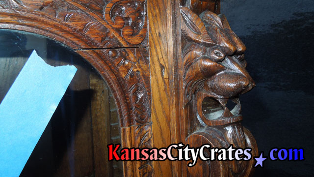 Close up view of lion head hand carved into antique furniture.