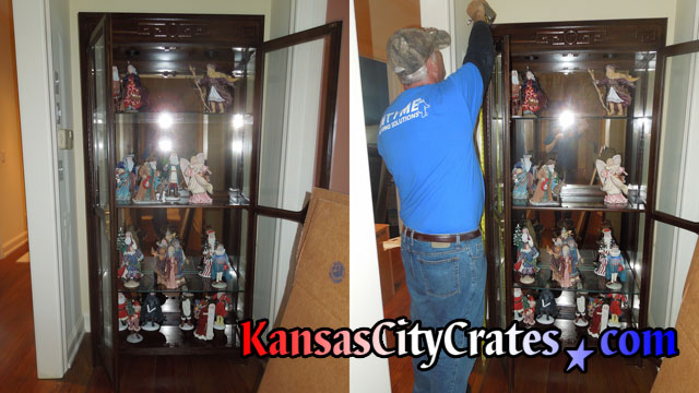 Original glass in antique china cabinet being measured for crating.