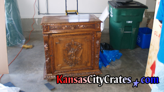 Antique hand carved cabinet with reversible door for summer or winter seasons before crating.