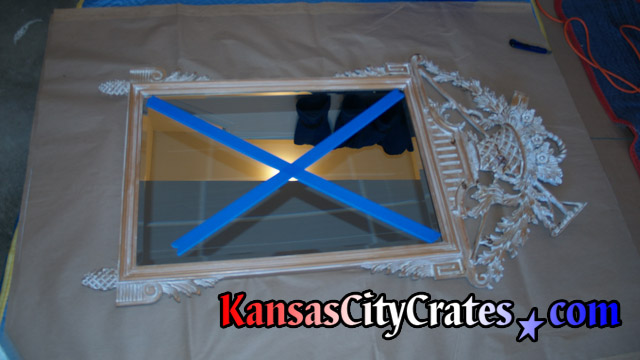 Blue painters tape on antique mirror with delicate crown.