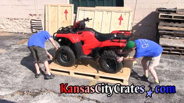 All 4 tires on ATV are secured to pallet by crate staff