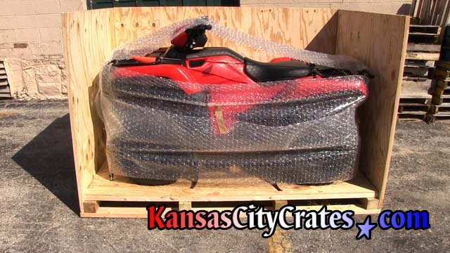 Side view of crate showing ATV bubble wrapped and secured to crate floor with tire bonnets.