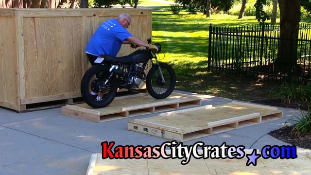 Loading restored vintage motorcycle onto crate pallet