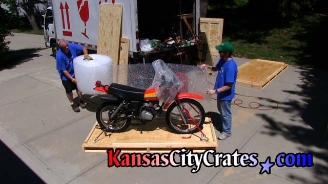 Personnel wrap dirt bike in bubble wrap to protect it during crating