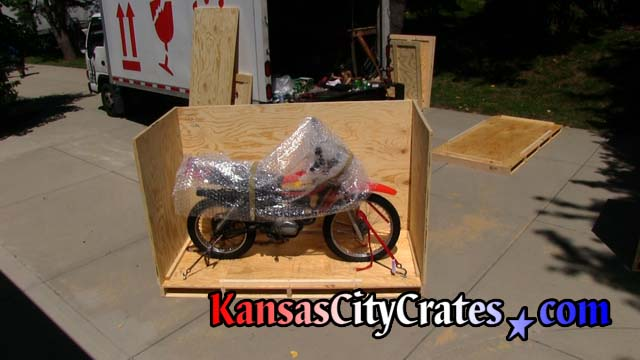 End panel of crate at rear of motorcycle attached.  View shows motorcyle strapped to floor of crate and the motorcycle bubble wrapped