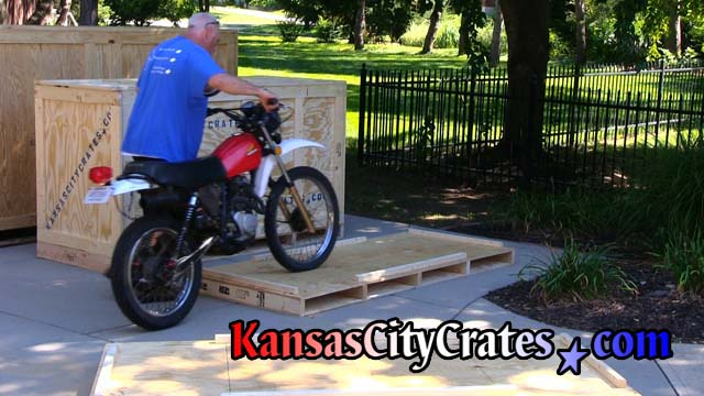 Crater rolls 1980 Dirt bike onto pallet floor of crate