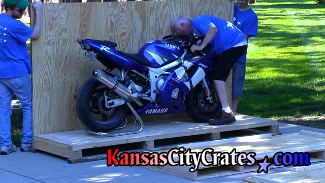 Personnel placing sidewall of crate onto pallet to check position of  motorcycle
