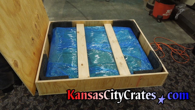 View of wood crate with lid removed showing  oil painting fully packaged and foam lining on shipping edges at Federal Government Office in Kansas City MO 64198