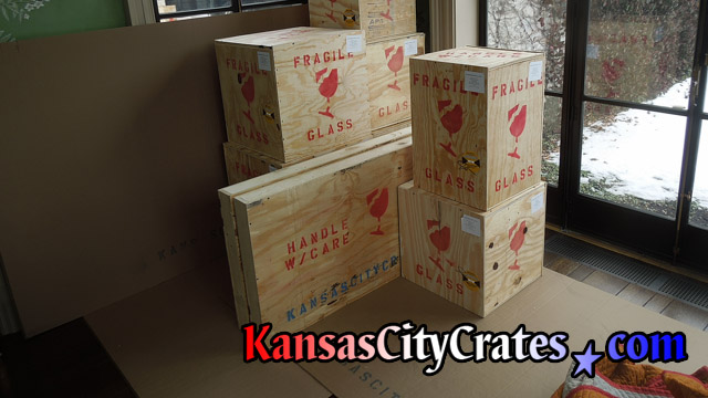 9 solid wall wood crates marked for shipment with Shockwatch impact indicators and content identification labels at home in Overland Park KS  66209