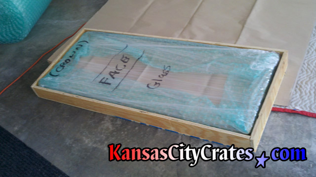 Plywood sheathed crate wood box containing fully wrapped mirror at home in Kansas City KS  66111
