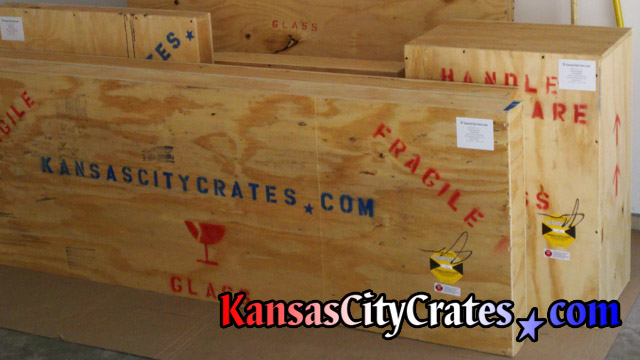 Solid wall wood crates with shipping symbols and shockwatch indicators staged on flooring protection for laoding at home in Lenexa KS  66015