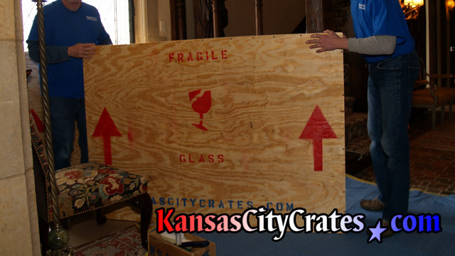 Crate is moved onto flooring protection before loading into transportation container at home in Overland Park KS  66204
