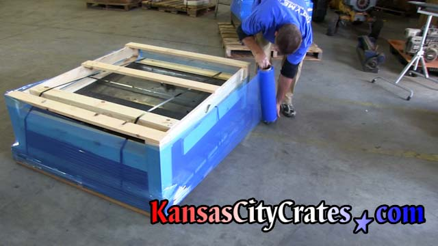 Stretch wrapping open frame crate steel strapped onto pallet with corner guards.