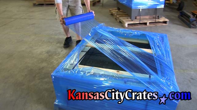 Covering top of open frame crate with stretch wrap.